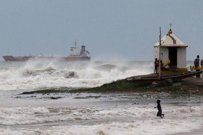 An Indian youth is pictured in the surf as large waves hit the beach ahead of Cyclone Hudhud making expected landfall in Visakhapatnam on Oct 11, 2014.India placed its navy on high alert and evacuated around 350,000 people from eastern coastal
