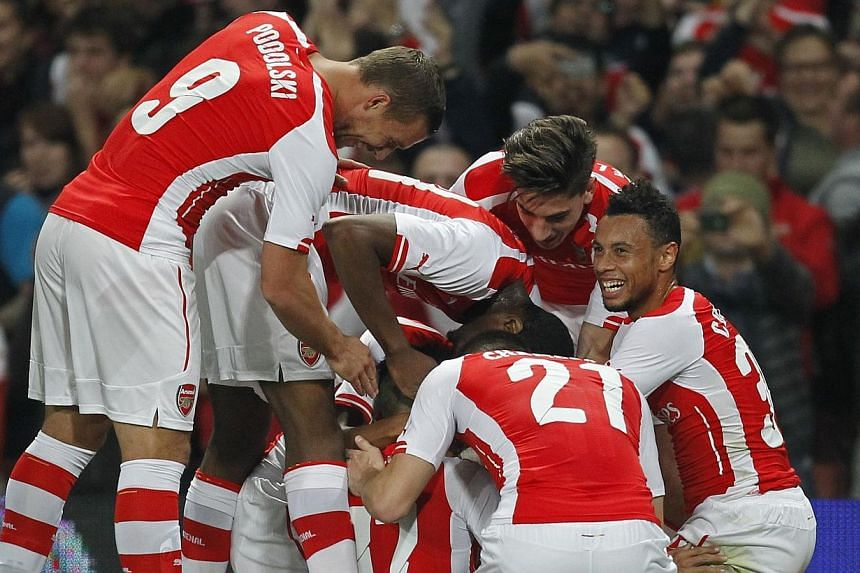 Arsenal's Chilean striker Alexis Sanchez celebrates scoring the opening goal with teammates during the English League Cup third round football match between Arsenal and Southampton at The Emirates Stadium in London on Sept 23, 2014. -- PHOTO: AFP