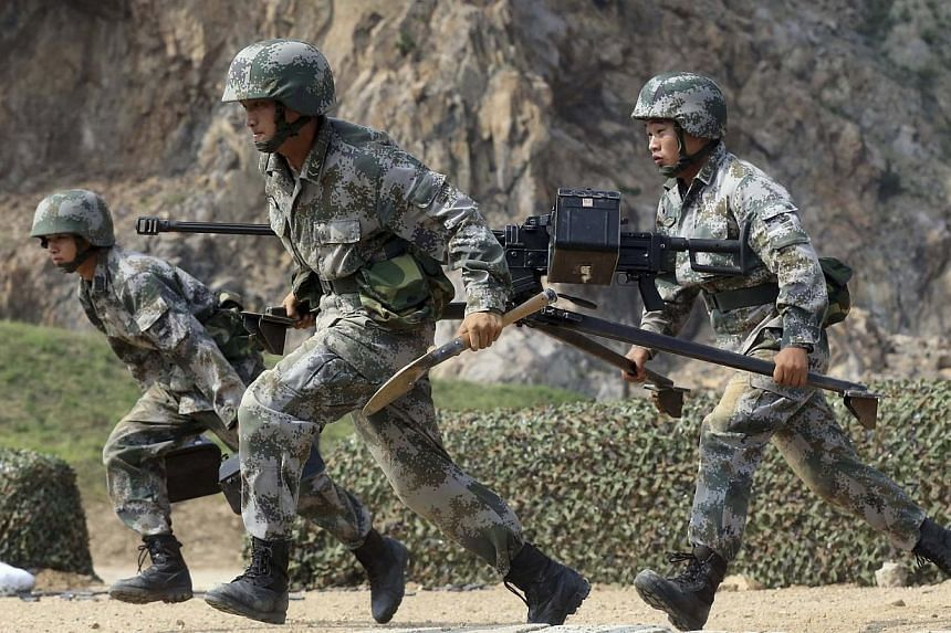 Members of the People's Liberation Army (PLA) coastal defence force carry a machine gun during a drill to mark the upcoming 87th Army Day at a military base in Qingdao, Shandong province on July 29, 2014. Weaknesses in China's military training