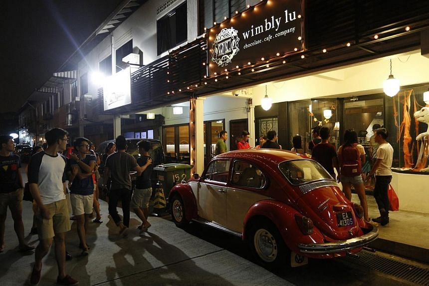 Visitors walk past rows of parked vehicles, located alongside the many eateries at Jalan Riang on Oct 11, 2014.The Urban Redevelopment Authority (URA) has banned more new restaurants from setting up shop in seven locations to prevent parking pr