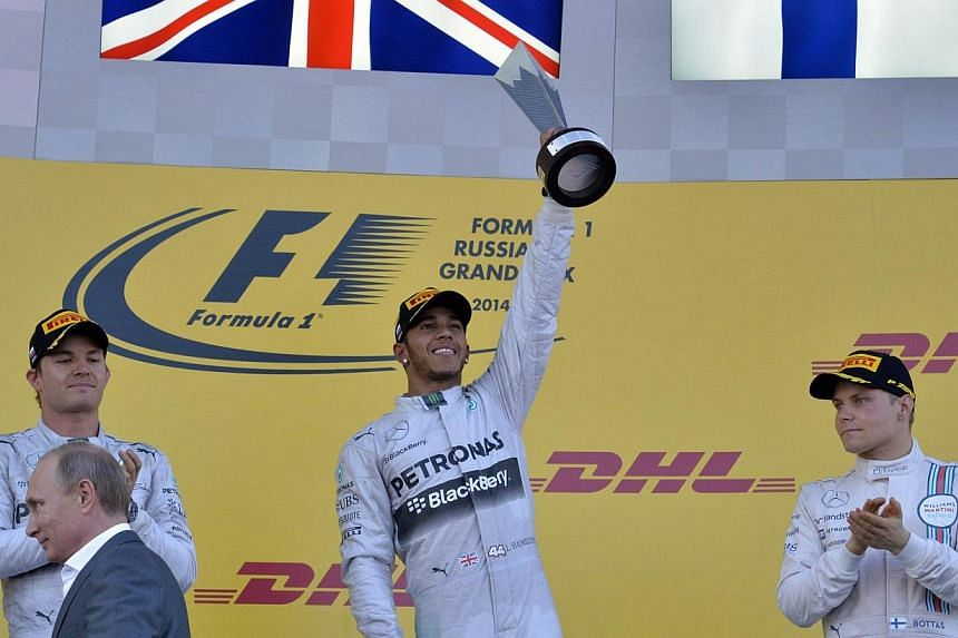 Mercedes' British driver Lewis Hamilton (centre) celebrates on the podium after winning the inaugural Russian Formula 1 Grand Prix at the Sochi Autodrom in Sochi on Oct 12, 2014. -- PHOTO: AFP