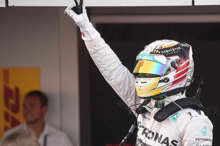 Mercedes' British driver Lewis Hamilton raises his arm after winning the inaugural Russian Formula 1 Grand Prix at the Sochi Autodrom in Sochi on Oct 12, 2014. -- PHOTO: AFP