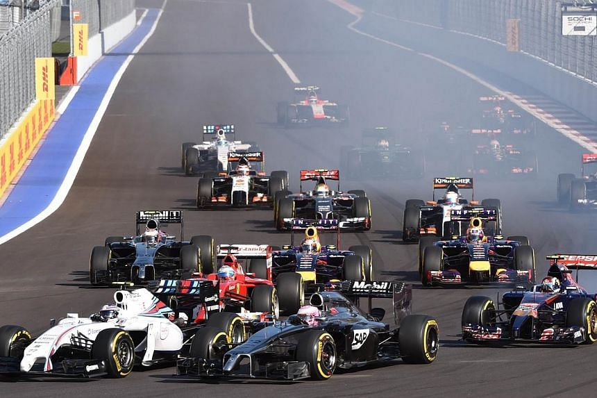 Williams' Finnish driver Valtteri Bottas (left) and McLaren Mercedes' British driver Jenson Button take the first corner during the inaugural Russian Formula 1 Grand Prix at the Sochi Autodrom in Sochi on Oct 12, 2014. -- PHOTO: AFP