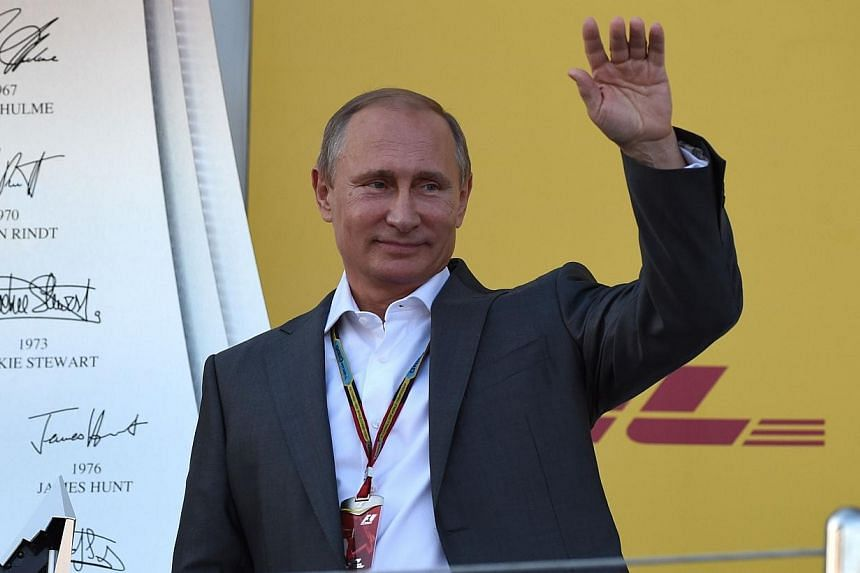 Russian President Vladimir Putin waves from the podium after the inaugural Russian Formula 1 Grand Prix at the Sochi Autodrom in Sochi on Oct 12, 2014. -- PHOTO: AFP
