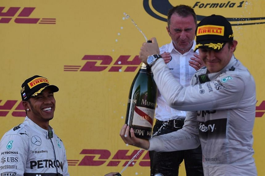 Second placed Mercedes' German driver Nico Rosberg (right), Mercedes co-team boss Paddy Lowe (centre) and winner Mercedes' British driver Lewis Hamilton spray champagne on the podium after the inaugural Russian Formula 1 Grand Prix at the Sochi Autod