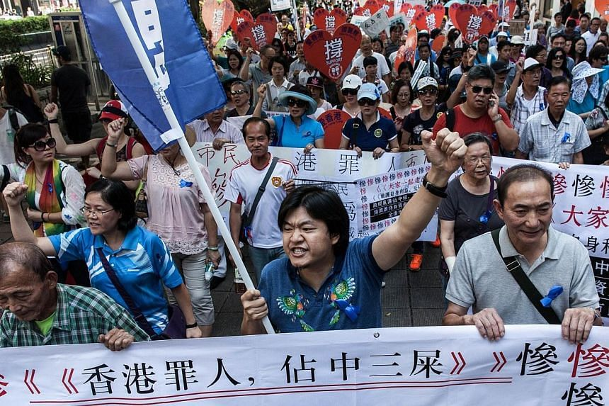 """Anti Occupy """"Blue Ribbon"""" group members shout slogans as they take part in a protest march towards an area near the Occupy camp in the Mong Kok district of Hong Kong on Oct 12, 2014.As the Occupy Central movement enters its third week with no e"""