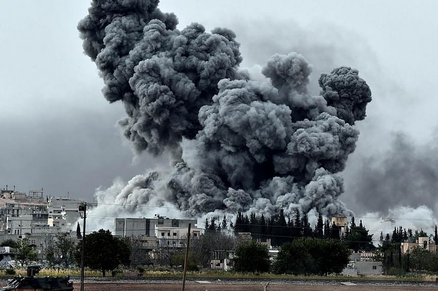 Smoke rises after a strike on the Syrian town of Ain al-Arab, known as Kobane by the Kurds, as seen from the Turkish-Syrian border, in the southeastern village of Mursitpinar, Sanliurfa province, on Oct 12, 2014.Islamic State in Iraq and Syria