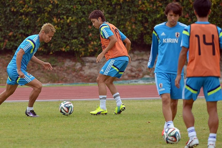 Keisuke Honda (left) takes on his teammate during training at Bishan Stadium on Sunday, Oct 12, where the Japan national football team was having its first training session ahead of their friendly match against Brazil on Tuesday. -- ST PHOTO: DESMOND