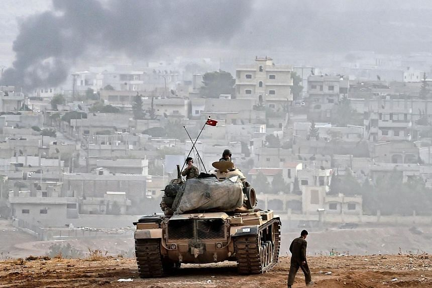 Turkish soldiers on a tank sit opposite the Syrian town of Ain al-Arab, known as Kobane by the Kurds, at the Turkish-Syrian border in the southeastern Turkish village of Mursitpinar, Sanliurfa province, on Oct 11, 2014.A Kurdish woman fighter i