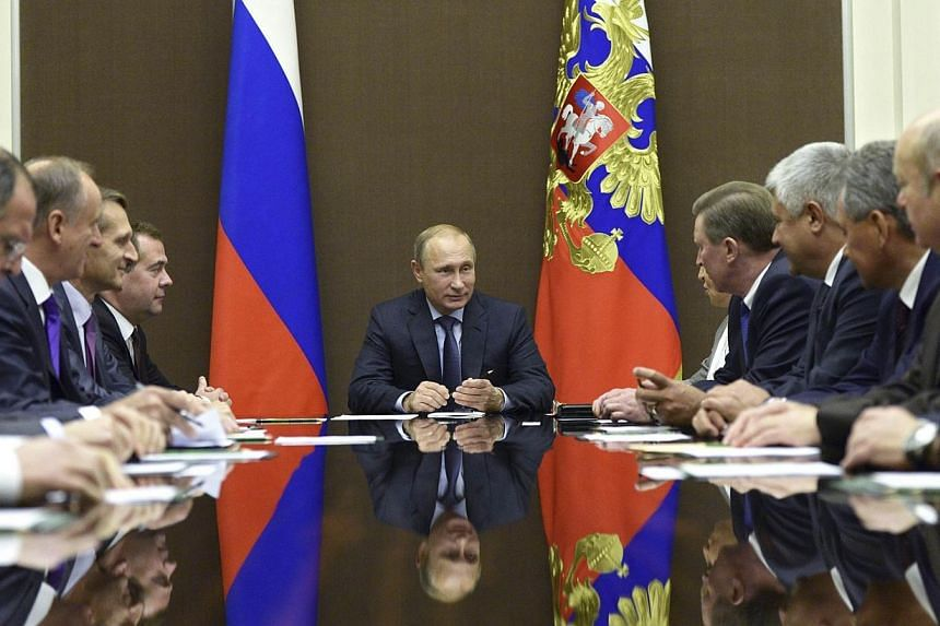Russia's President Vladimir Putin (centre) chairs a meeting of the Security Council at the Bocharov Ruchei state residence in Sochi, on Oct 11, 2014.Mr Putin has ordered Russian troops to withdraw to their permanent bases after military exercis