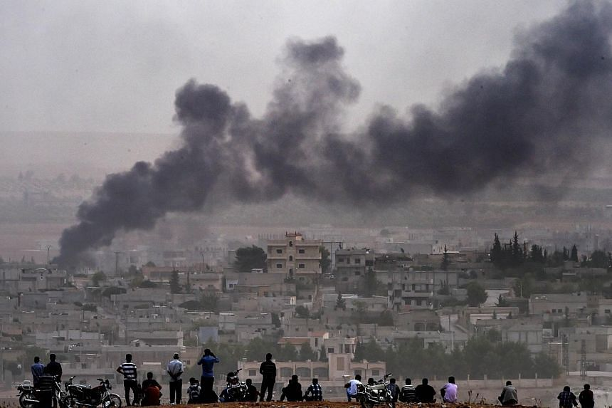 Kurdish people look at smoke rising from the Syrian town of Ain al-Arab, known as Kobane by the Kurds, from the Turkish-Syrian border, on Oct 11, 2014 in Mursitpinar, Sanliurfa province.The Islamic State in Iraq and Syria (ISIS) group poured in