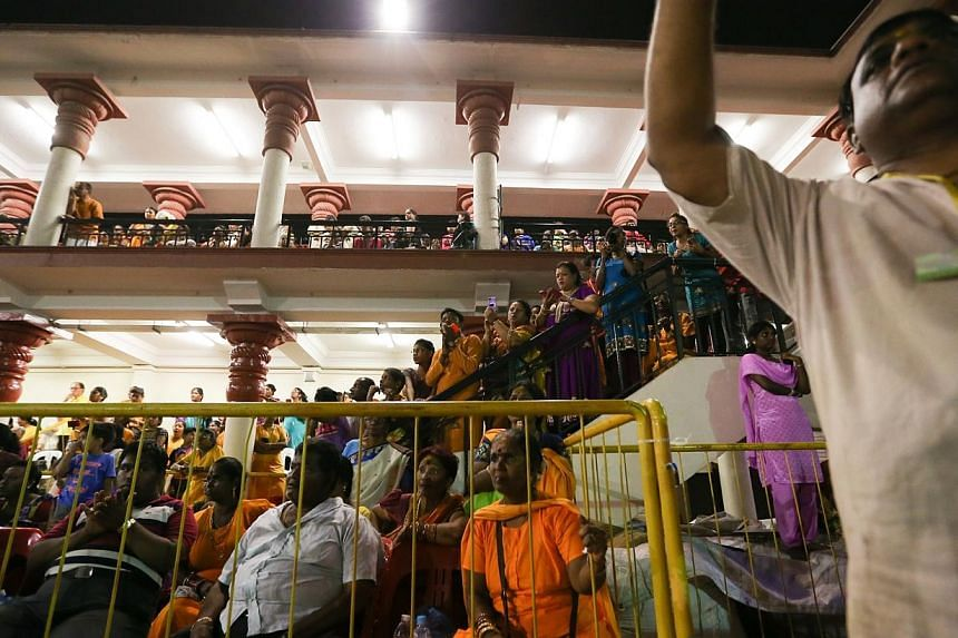 Spectators at the annual fire walking festival for Hindu devotees at Sri Mariamman Temple. -- ST PHOTO: ONG WEE JIN