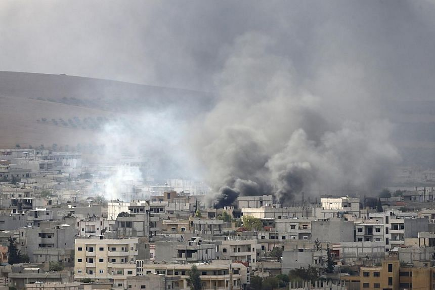 """Smoke rises from the Syrian town of Kobane, near the Turkish-Syrian border on Oct 12, 2014.UN chief Ban Ki Moon Sunday urged action to prevent a """"massacre"""" of civilians in Kobane, saying thousands of lives were at stake as militants battled Kur"""