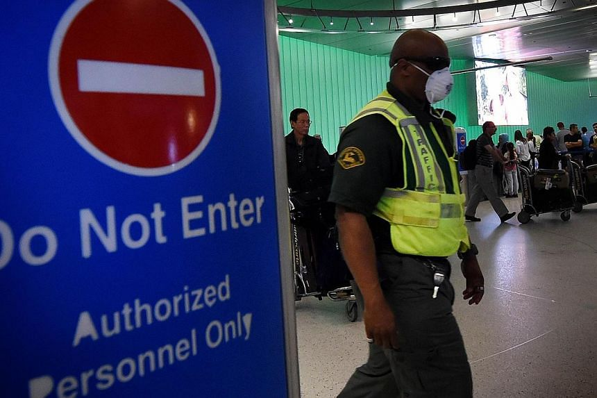 An airport worker wears a protective face mask in the arrivals area of the Los Angeles International Airport as the US announced increased passenger screenings against the Ebola Virus on Oct 9, 2014.A Texas health care worker who treated an Ebo