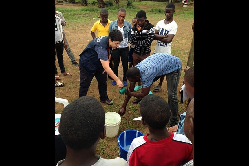 Associate Professor Fisher in Liberia with children separated from their parents - possible Ebola victims - but who have tested negative. Nurse Sharon Salmon shows villagers how to wash their hands with the right mix of chlorine and water to disinfec