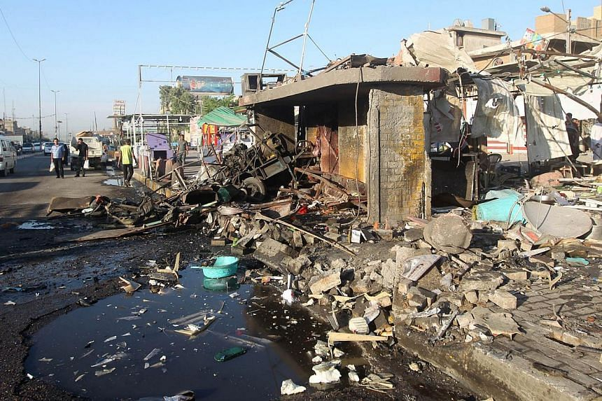A picture shows the site of an explosion in the aftermath of a car bomb attack in the mostly Shiite Sadr City district of Baghdad on Oct 9, 2014. -- PHOTO: AFP