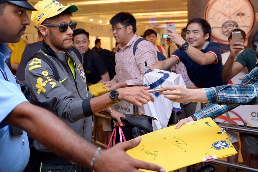 Neymar Jr (with sunglasses) signing autographs for fans.-- ST PHOTO: LIM SIN THAI