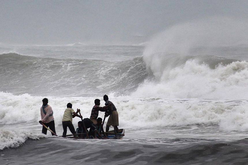 Indian fishermen negotiate their skiff through rough waves ahead of Cyclone Hudhud making expected landfall in Visakhapatnam on Oct 11, 2014. -- PHOTO: AFP