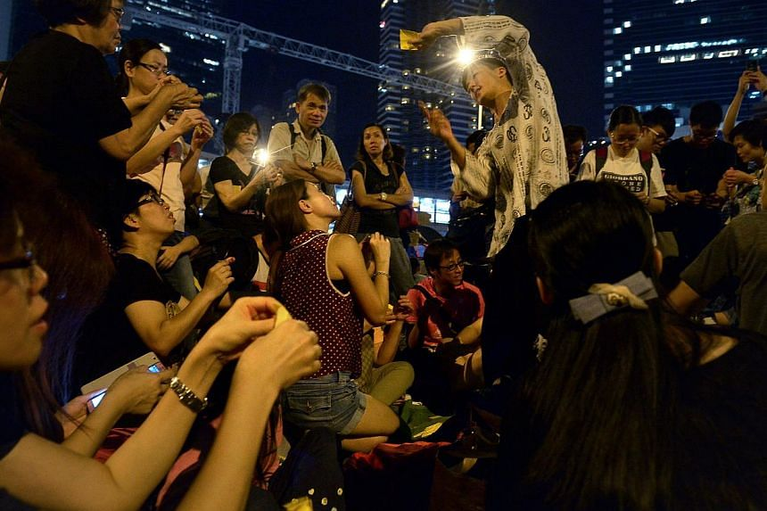 Henry Fung, 30 (centre) teaches a crowd of protesters how to fold origami umbrellas which will be hung from the pedestrain overhead bridge over Harcourt Road, the main protest site in Admiralty, Hong Kong. -- ST PHOTO: KUA CHEE SIONG