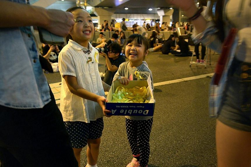Winni Chan, 5 (left) and Chloe Lo, 4 (right) who just became friends at the protest site, distribute yellow ribbons to passers-by at Harcourt Road in Admiralty, Hong Kong. -- ST PHOTO: KUA CHEE SIONG