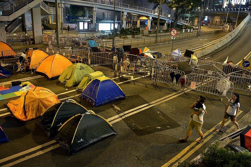 A couple carrying their baby walk past tents and barricades near Harcourt Road in Admiralty, the main protest site in Hong Kong on Oct 11, 2014. -- ST PHOTO: KUA CHEE SIONG