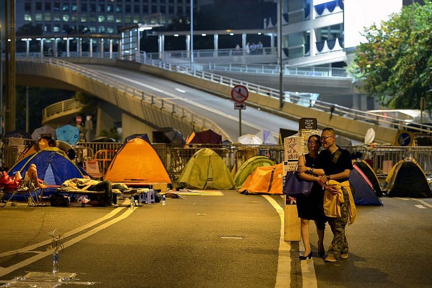 A couple walk past tents and barricades near Harcourt Road in Admiralty, the main protest site in Hong Kong on Oct 11, 2014. -- ST PHOTO: KUA CHEE SIONG