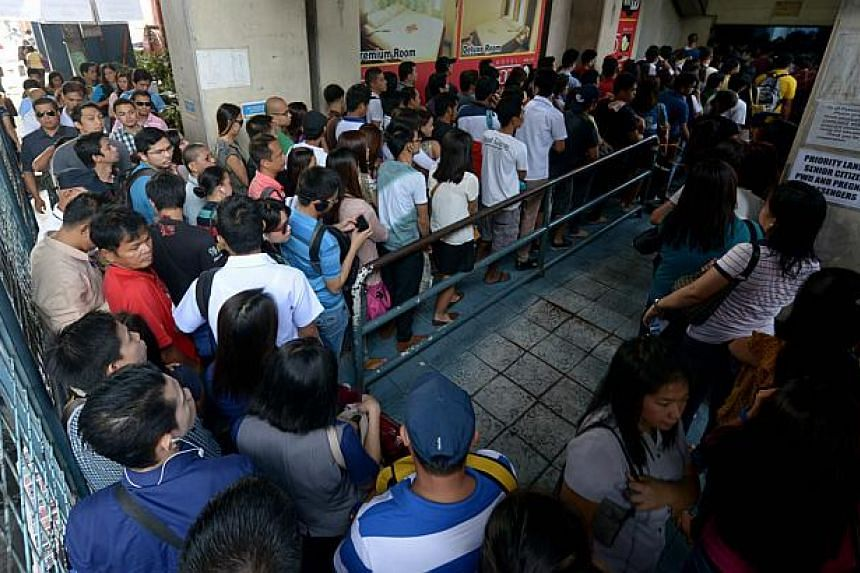 Commuters queuing to ride the Light rail transit in Quezon City, suburban Manila, on Oct 10, 2014. Peak-hour hell comes in many forms in the Philippine capital. For computer salesman Gerard Galang it is the sweaty, stinky crush on dilapidated trains
