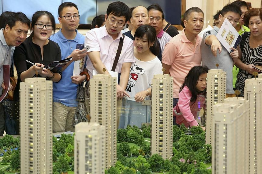 Customers look at a model of a new residential compound at a showroom in Hangzhou, Zhejiang province in this Aug 17, 2014 file picture.The chance of a hard landing for China's economy is very small in spite of worries about the country's real-e