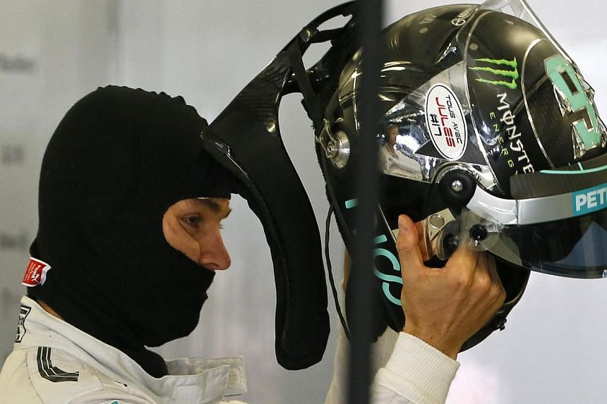 Mercedes Formula One driver Nico Rosberg of Germany puts on a helmet displaying a sticker in support of Marussia Formula One driver Jules Bianchi during the third free practice session at the Russian F1 Grand Prix in the Sochi Autodrom circuit Oct 11