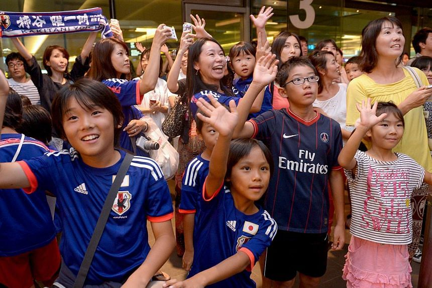 Fans awaiting the arrival of Japan's national soccer team at Changi Airport on Oct 11, 2014. About 300 fans turned up, with about 200 of them Japanese.-- PHOTO: LIM SIN THAI