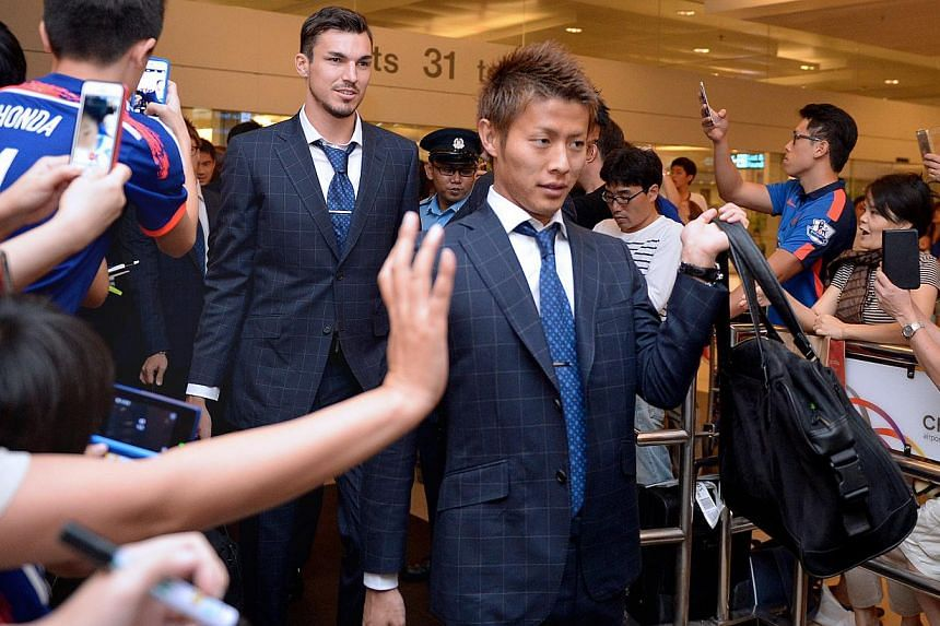 Japan's national football team arriving at Changi Airport on Oct 11, 2014. The Asian Cup champions are in town to play Brazil at the National Stadium on Tuesday.-- PHOTO: LIM SIN THAI
