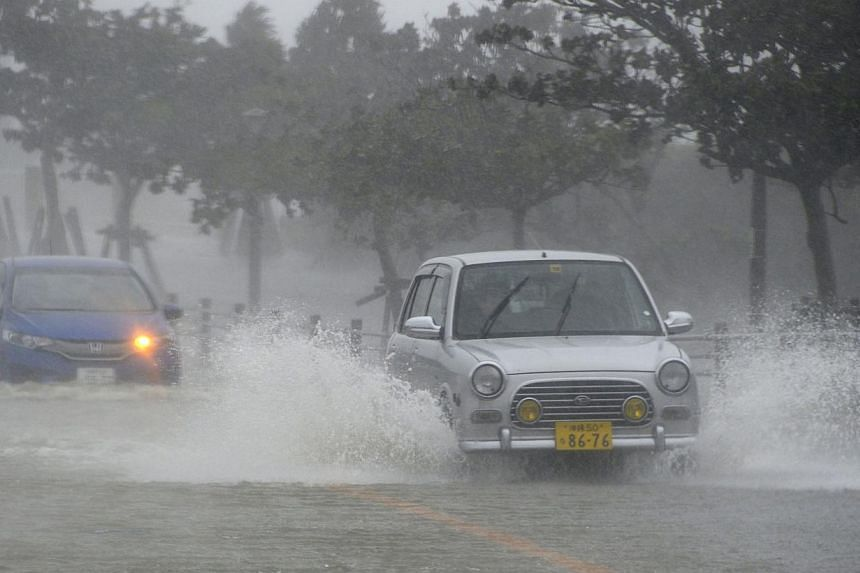 Cars drive on a waterlogged road due to heavy rain caused by approaching Typhoon Vongfong in Nishihara town on Japan's southern island of Okinawa, in this photo taken by Kyodo on Oct 11, 2014. -- PHOTO: REUTERS