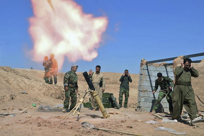Kurdish fighters fire a mortar during clashes with Islamic State militants in the al-Zerga area near Tikrit city, in Salahuddin province on Oct 8, 2014. -- PHOTO: REUTERS