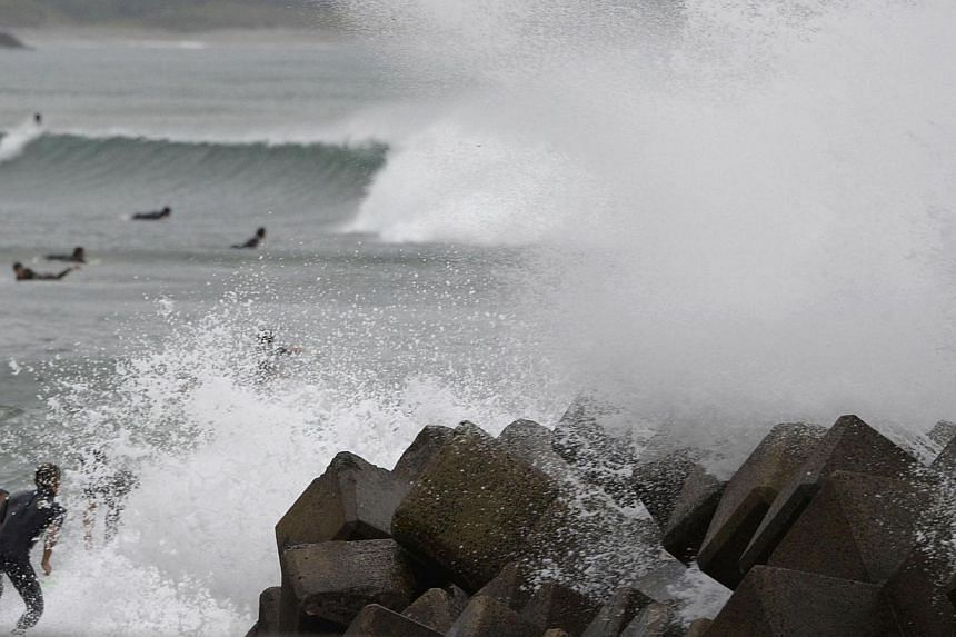 Waves crash as Typhoon Vongfong approaches Japan's main islands while surfers try to ride a wave at Eguchihama Beach in Hioki, Kagoshima prefectureon Oct 12, 2014. -- PHOTO: REUTERS