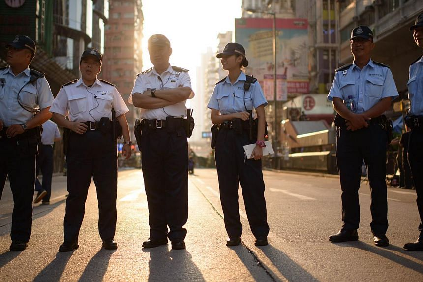 Police stand on a road occupied by pro-democracy protesters in the Mong Kok district of Hong Kong on Oct 12, 2014. -- PHOTO: AFP