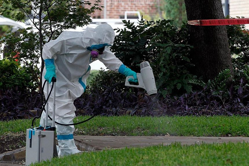 A man dressed in protective hazmat clothing treats the sidewalk in front of an apartment where a second person diagnosed with the Ebola virus resides on Oct 12, 2014, in Dallas, Texas. -- PHOTO: AFP