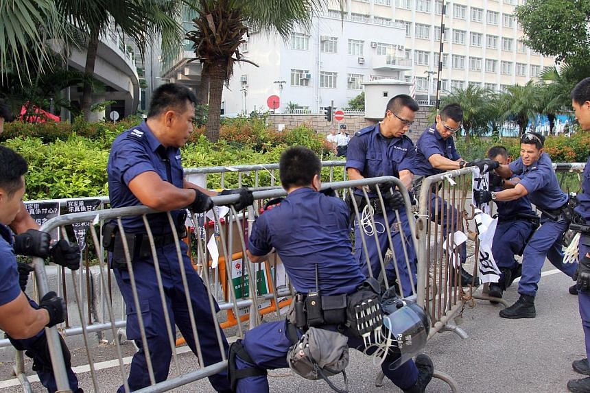 Police officers remove barricades from pro-democracy demonstrators (unseen) near the government offices in Hong Kong on Oct 13, 2014. -- PHOTO: AFP