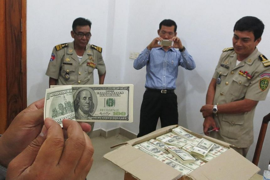 Police and court officials examine notes from a seized haul of US$7.16 million (S$9.1 million) in counterfeit hundred-dollar bills, in Battambang on Sept 30, 2014. -- PHOTO:REUTERS