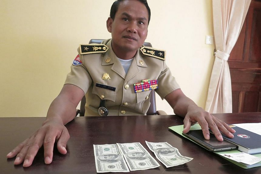 Battambang's police chief, Brigadier General Sar Theth, poses with notes from a seized haul of US$7.16 million (S$9.1 million)in counterfeit hundred-dollar bills, in Battambang on Sept 30, 2014.-- PHOTO:REUTERS