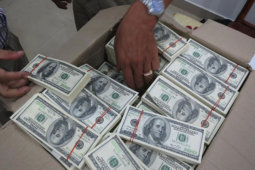 Police and court officials examine notes from a seized haul of US$7.16 million (S$9.1 million)in counterfeit hundred-dollar bills, in Battambang on Sept 30, 2014.-- PHOTO:REUTERS