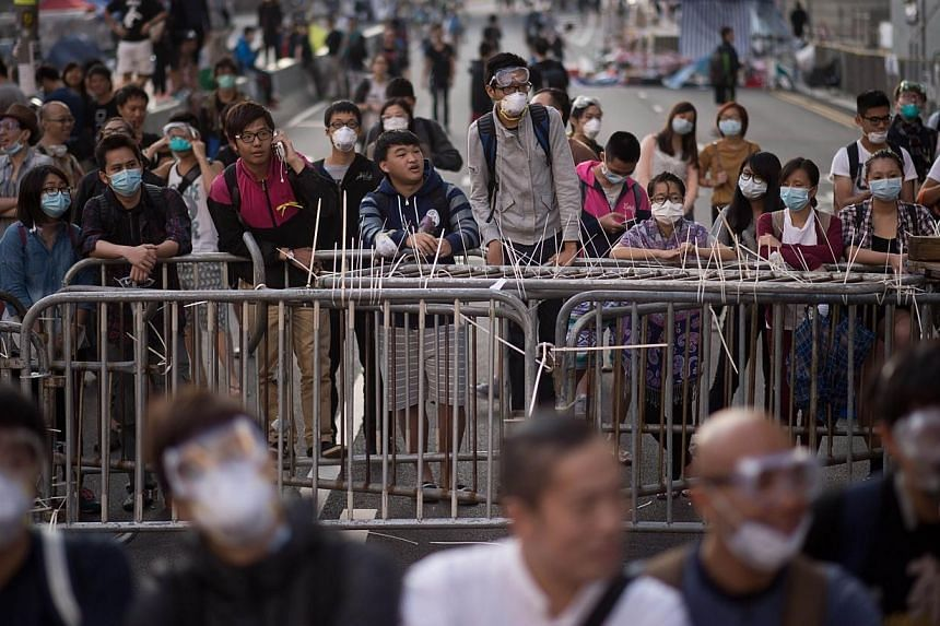 Pro-democracy protesters gather near barricades in the Admiralty district of Hong Kong on Oct 13, 2014.The pro-democracy demonstrators are winning unexpected support from pockets of the city's much-vilified mainland Chinese community, who are d