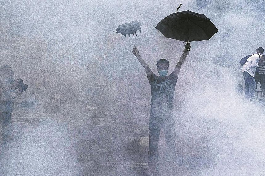 A pro-democracy demonstrator gestures after police fired tear gas towards protesters near the Hong Kong government headquarters on Sept 28, 2014.Denying his involvement in a tear gas attack last month on protestors calling for free elections in