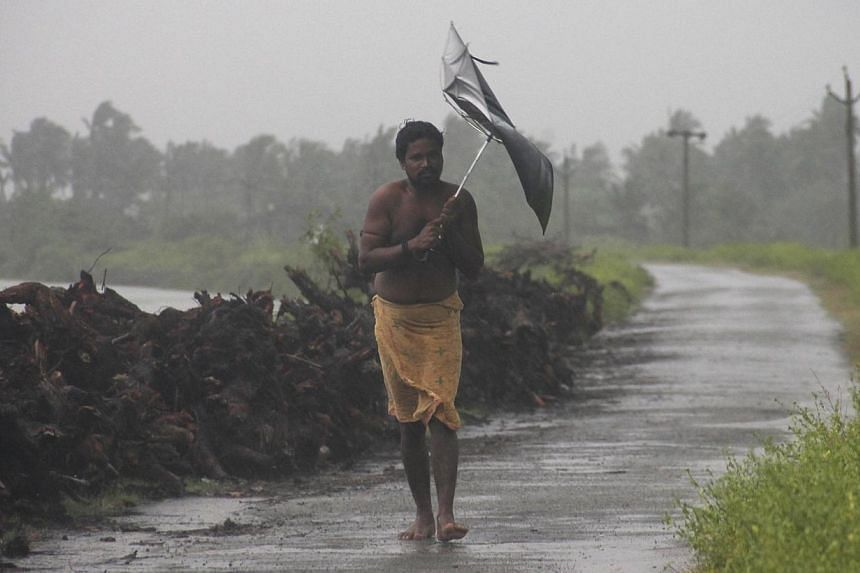 A man struggles with an umbrella in strong winds and rain caused by Cyclone Hudhud in Gopalpur in Ganjam district in the eastern Indian state of Odisha on Oct 12, 2014. A major relief operation was under way on Monday after the cyclone pounded I