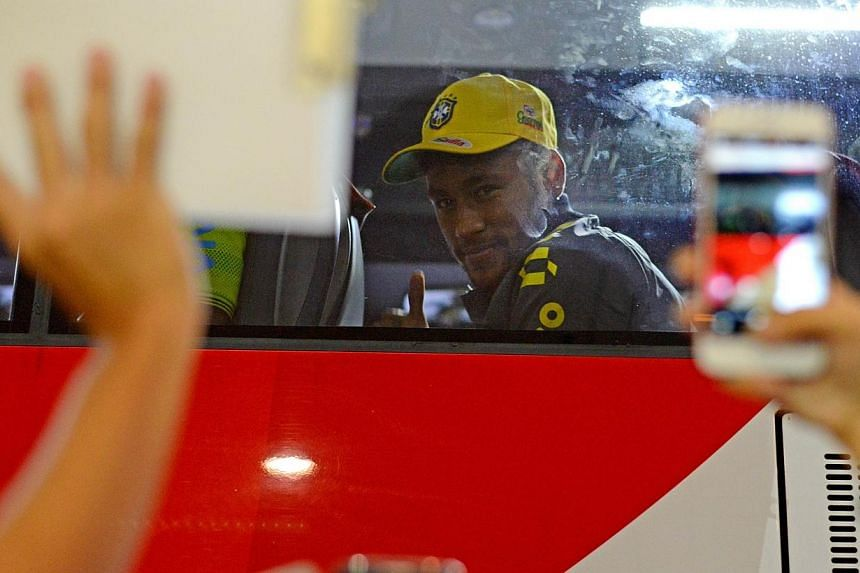 Brazil National player Neymar gestures to fans at Changi Airport together with his teammates in Singapore on Oct 12, 2014. Fans hoping to catch a glimpse of superstars Neymar and Kaka in action will have to wait until Tuesday's game against Japa