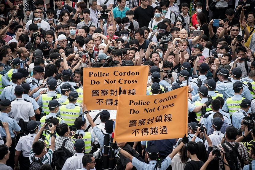 Policemen cordon an area where pro-democracy demonstrators confronted anti-occupy protesters (not in picture) in the Admiralty district of Hong Kong on Oct 13, 2014. With pro-government and pro-democracy protestors now going head to head in Hong