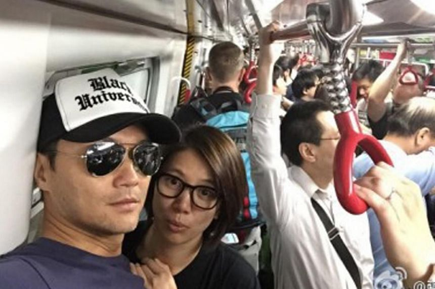 Actor Julian Cheung with his wife, actress-singer Anita Yuen on the MTR. -- PHOTO: JULIAN CHEUNG'S WEIBO