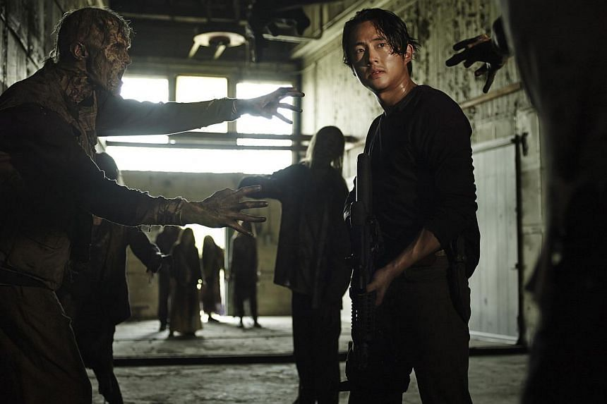 Main characters in The Walking Dead that are favourites with fans are played by Steven Yeun (right), Andrew Lincoln and Norman Reedus. -- PHOTO: FOX INTERNATIONAL CHANNELS