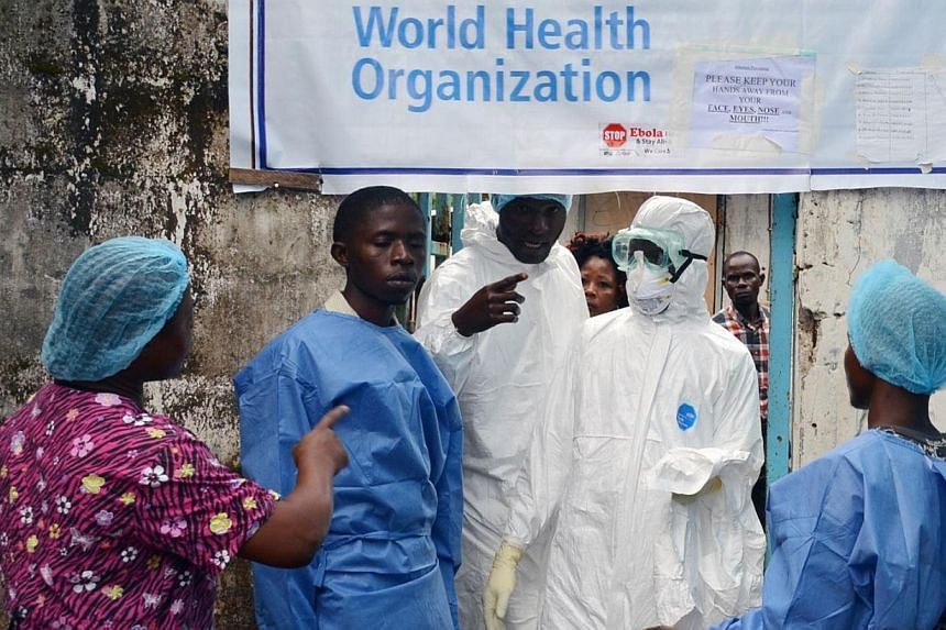 Health workers in protective gear pose at the entrance of the Ebola treatment unit of the John F. Kennedy Medical Center, in the Liberian capital Monrovia, on Oct 13, 2014. Many Liberian healthcare workers on the frontline of the battle against