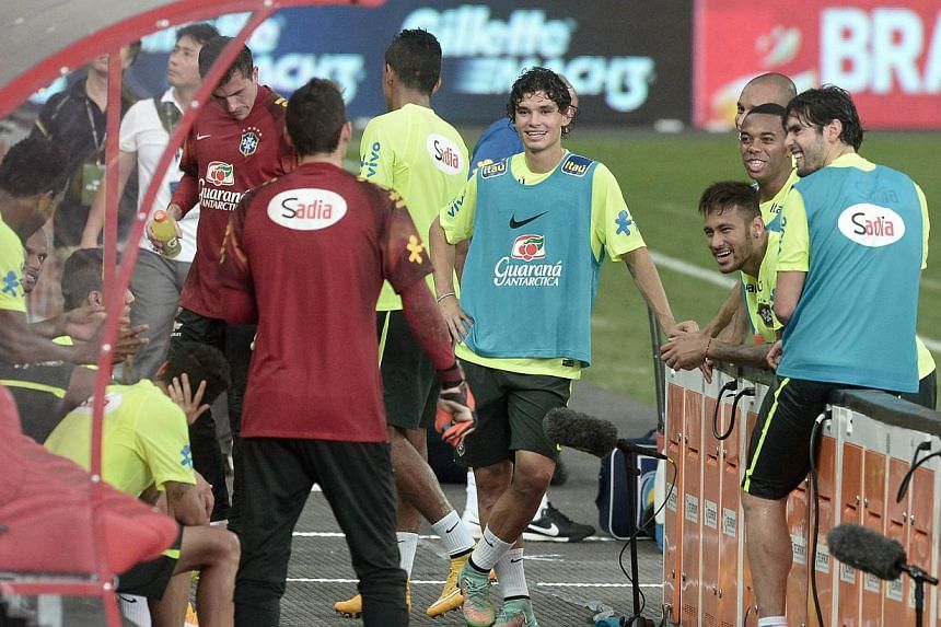 Brazil's players chat after their football training session at the new National stadium in Singapore on Oct 13, 2014. -- PHOTO: AFP