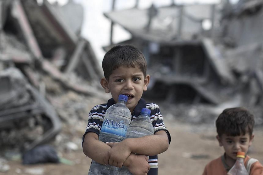 Palestinian children carrying bottles of water walk past buildings which were destroyed by Israeli military strikes during the summer's fierce offensive, on October 1, 2014, in the Shejaiya neighborhood of Gaza City.. -- PHOTO: AFP